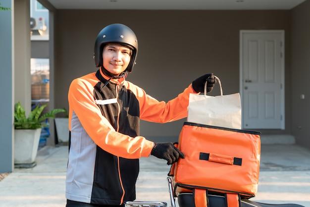 Levering aziatische man met oranje uniform en klaar om te sturen leveren van voedsel Premium Foto