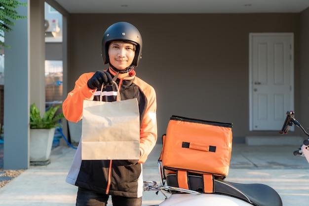 Levering aziatische mens die oranje eenvormig en klaar om het verzenden van voedselzak voor klant houes met de doos van het voedselgeval op autoped, uitdrukkelijke voedsellevering en het winkelen online concept te verzenden. Premium Foto