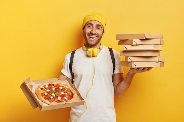 Levering concept. man pizzadealer houdt stapel op kartonnen dozen, toont lekker fastfood in geopende container, werkt als koerier, draagt gele hoed en wit t-shirt, koptelefoon gebruikt voor het luisteren naar audio. Gratis Foto