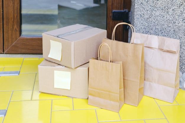 Levering dozen, papieren zakken voor de deur bij huisdeur. contactloze levering van voedsel. veilig winkelen e-commerce aankooppakketten naar huis. dozen per koerier, postbode bij de voordeur afgeleverd. Premium Foto