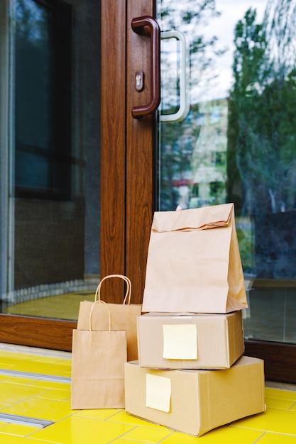 Levering dozen, papieren zakken voor de deur bij huisdeur. contactloze levering. veilig winkelen e-commerce aankooppakketten naar huis. dozen geleverd aan de voordeur. voorraad foto Premium Foto