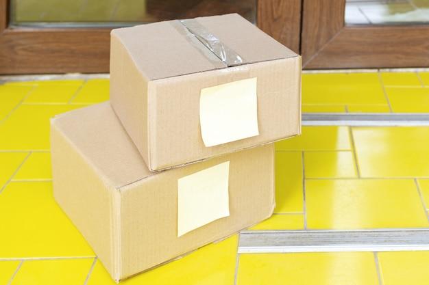 Levering dozen voor de deur in de buurt van huisdeur. contactloze levering van voedsel. veilig winkelen e-commerce pakketten thuis kopen. dozen per koerier, postbode aan de voordeur bezorgd Premium Foto