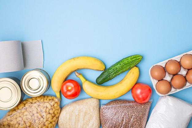 Levering eten. rijst, boekweit, pasta, ingeblikt voedsel, suiker, wc-papier op blauwe achtergrond. Premium Foto