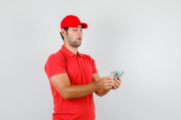 Levering man dollar biljetten tellen in rood t-shirt Gratis Foto