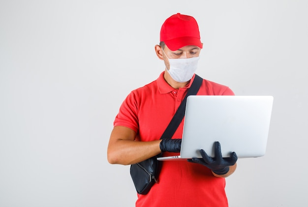 Levering man in rood uniform, medisch masker, handschoenen te typen op laptop Gratis Foto