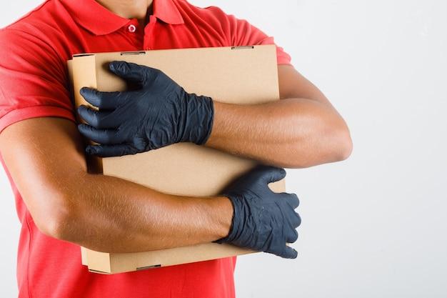 Levering man in rood uniform, medische handschoenen kartonnen doos knuffelen en er zelfverzekerd uitzien Gratis Foto