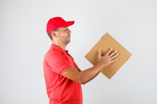 Levering man in rood uniform met pizzadoos. Gratis Foto