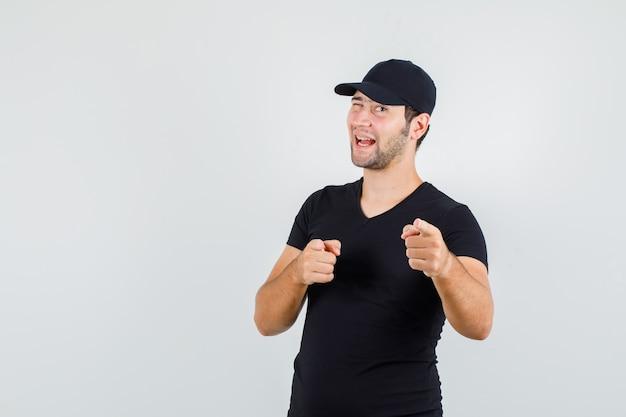 Levering man in zwart t-shirt, pet wijzend op camera met knipperende ogen en op zoek blij Gratis Foto