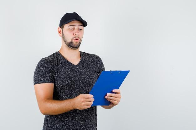 Levering man kijkt uit over notities op klembord in t-shirt en pet en kijkt voorzichtig Gratis Foto