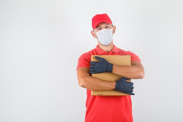 Levering man knuffelen kartonnen doos in rood uniform, medisch masker, handschoenen en er zelfverzekerd uitzien Gratis Foto