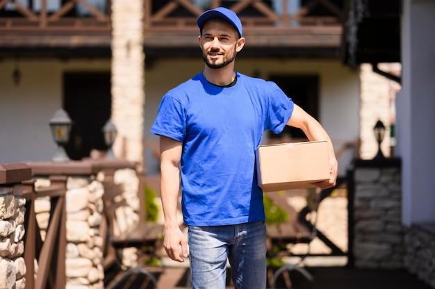 Levering man met kartonnen doos buitenshuis Gratis Foto