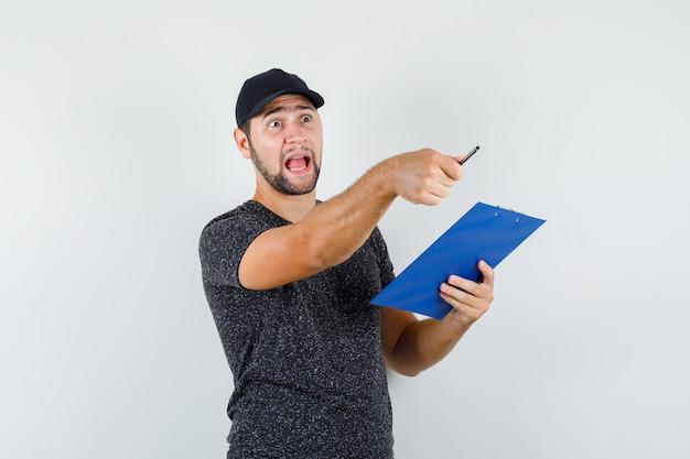 Levering man met klembord terwijl hij weg wijst in t-shirt en pet en boos kijkt Gratis Foto