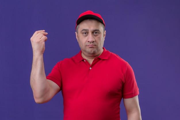 Levering man met rode uniform en pet ontevreden staan met opgeheven hand Gratis Foto