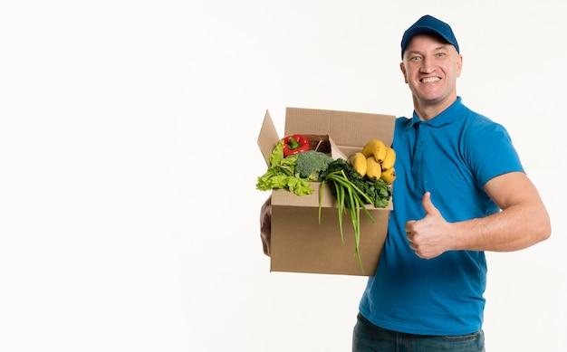 Levering man poseren met kruidenier doos en duimen omhoog Gratis Foto