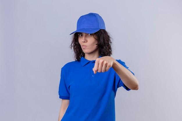 Levering meisje in blauw uniform en pet gebaren vuist hobbel alsof groet kijken met verdachte uitdrukking staande over geïsoleerde witte ruimte Gratis Foto