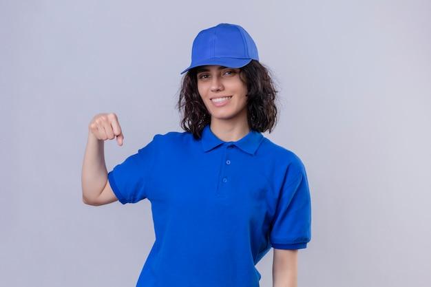 Levering meisje in blauw uniform en pet glimlachend vriendelijk gebaren vuist hobbel alsof groet, goedkeuren of als teken van respect staande op geïsoleerde wit Gratis Foto