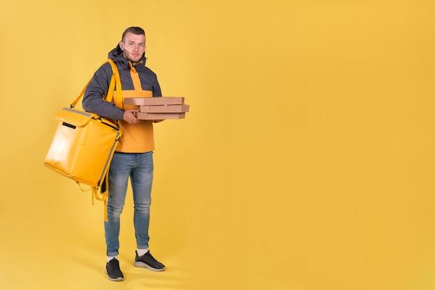 Levering van voedsel jonge man in een gele jas Premium Foto