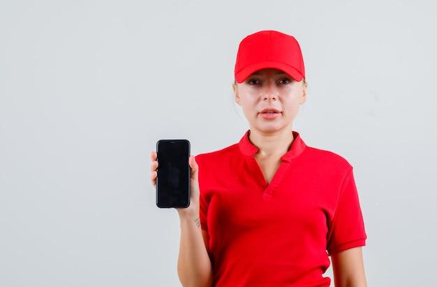 Levering vrouw in rood t-shirt en pet met mobiele telefoon Gratis Foto