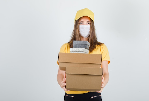 Levering vrouw met dozen in t-shirt, broek en pet, masker en op zoek vrolijk Gratis Foto