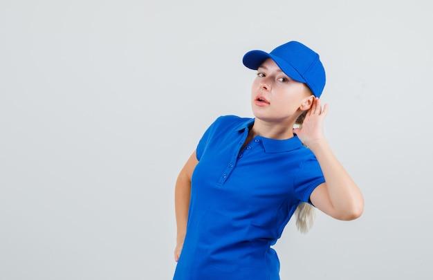 Levering vrouw met hand achter oor in blauw t-shirt en pet en nieuwsgierig kijken Gratis Foto