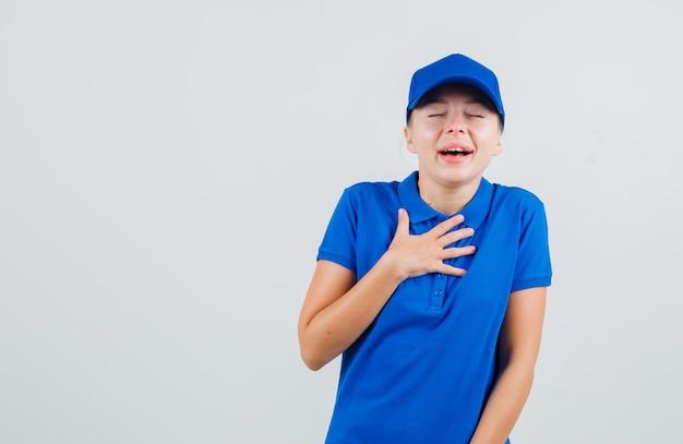Levering vrouw met hand op de borst in blauw t-shirt en pet en op zoek gelukkig Gratis Foto