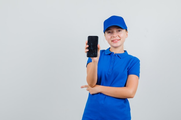 Levering vrouw met mobiele telefoon in blauw t-shirt en pet en op zoek vrolijk Gratis Foto