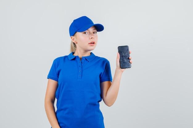 Levering vrouw met mobiele telefoon in blauw t-shirt en pet Gratis Foto