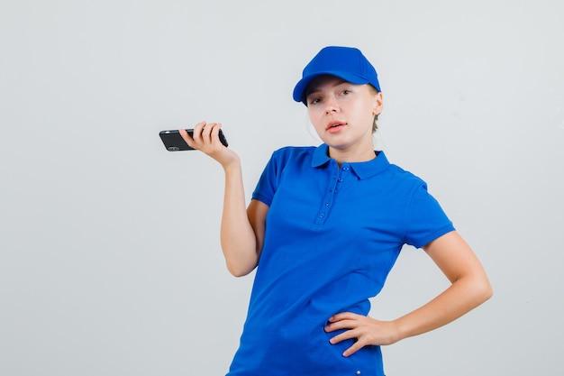 Levering vrouw met mobiele telefoon met hand op taille in blauw t-shirt en pet Gratis Foto