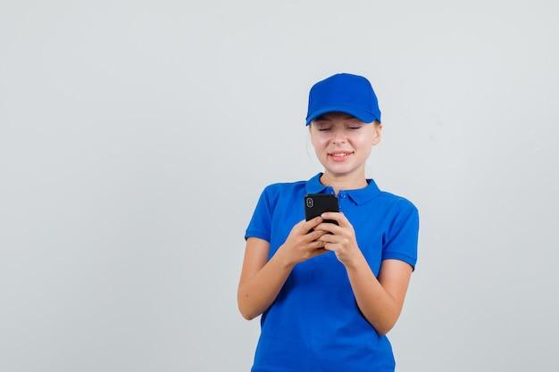 Levering vrouw met tekstchat op mobiele telefoon in blauw t-shirt en pet en op zoek vrolijk Gratis Foto