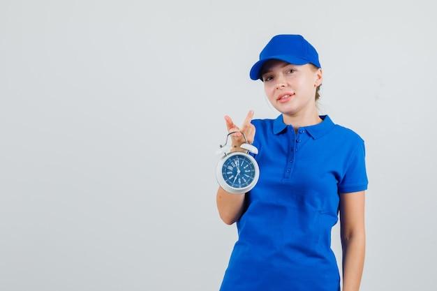 Levering vrouw met wekker en glimlachend in blauw t-shirt en pet Gratis Foto