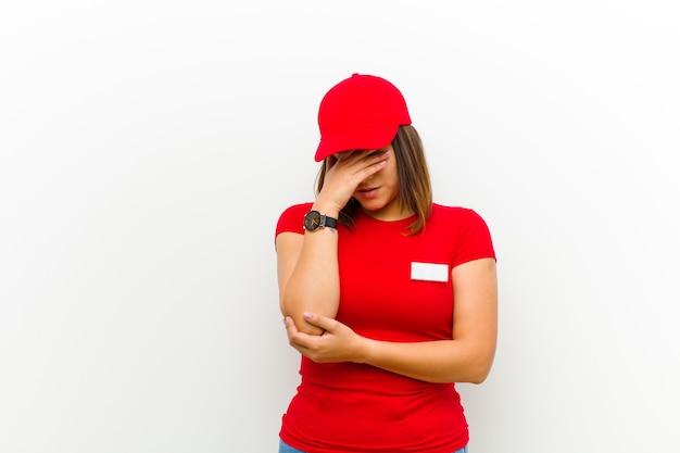 Levering vrouw op zoek gestresst, beschaamd of overstuur, met een hoofdpijn, die gezicht bedekt met de hand Premium Foto