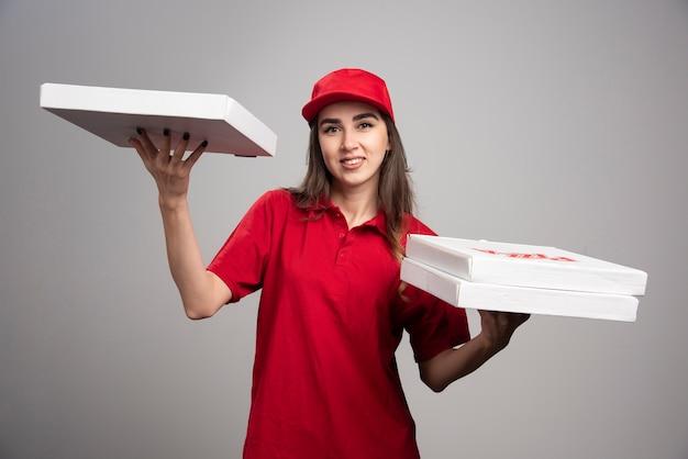 Levering vrouw poseren met pizza bestellingen. Gratis Foto