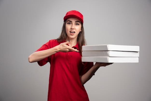 Levering vrouw wijzend op pizza's op grijze muur. Gratis Foto