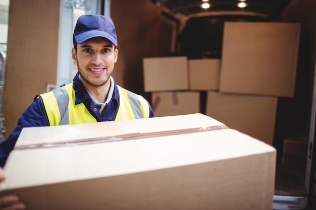 Leveringsbestuurder die bij camera door zijn pakket van de bestelwagenholding buiten het pakhuis glimlachen Premium Foto