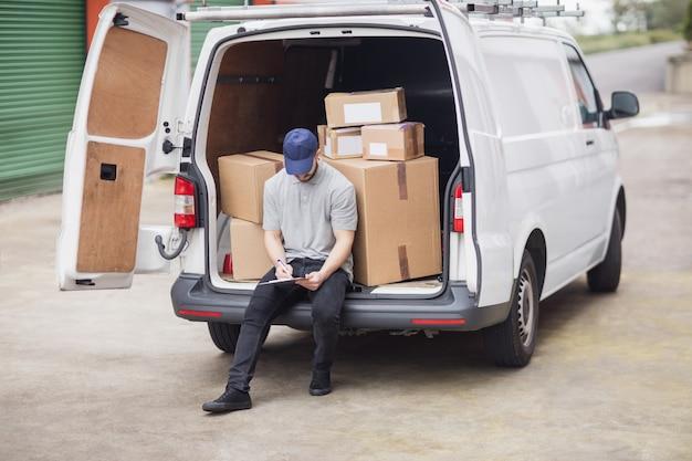 Leveringsmens die op klembord schrijven terwijl het zitten op de ladingsruimte van zijn bestelwagen Premium Foto