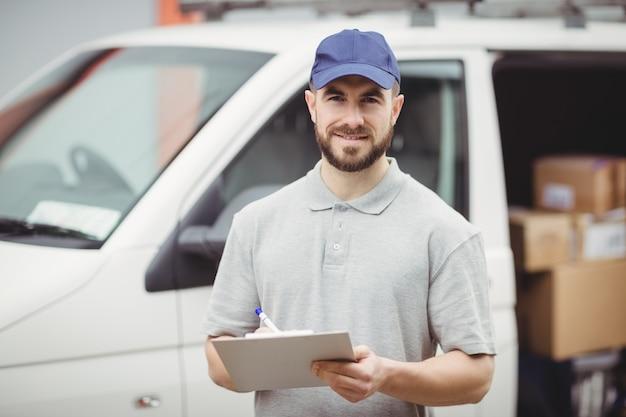 Leveringsmens die op klembord voor zijn bestelwagen schrijven Premium Foto
