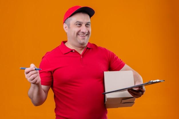 Leveringsmens die rood uniform en glb-het pakket en de klembord van de holdingsdoos met pen dragen die opzij met gelukkig gezicht kijken die over oranje muur glimlachen Gratis Foto