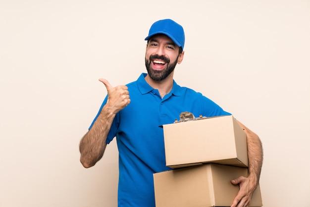 Leveringsmens met baard over geïsoleerd met duimen op gebaar en het glimlachen Premium Foto