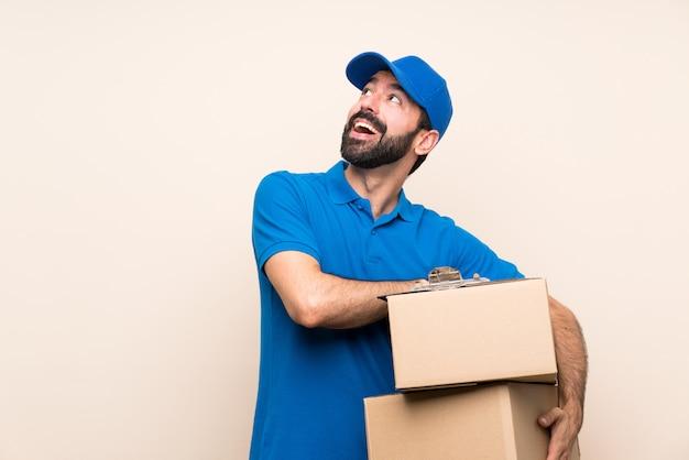 Leveringsmens met baard over het geïsoleerde omhoog kijken terwijl het glimlachen Premium Foto