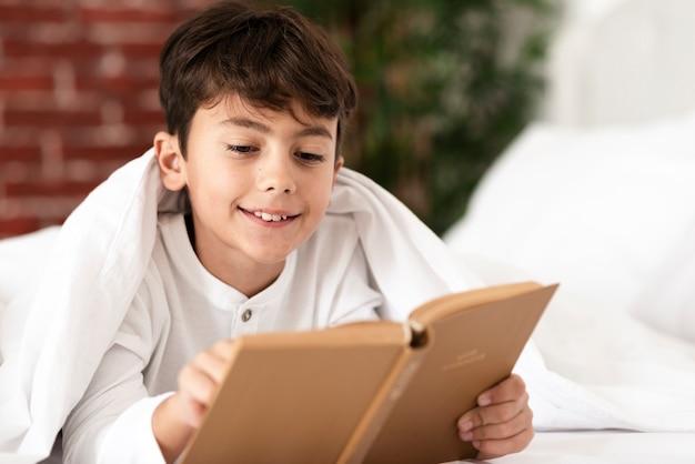 Lezingstijd met smiley jonge jongen Gratis Foto