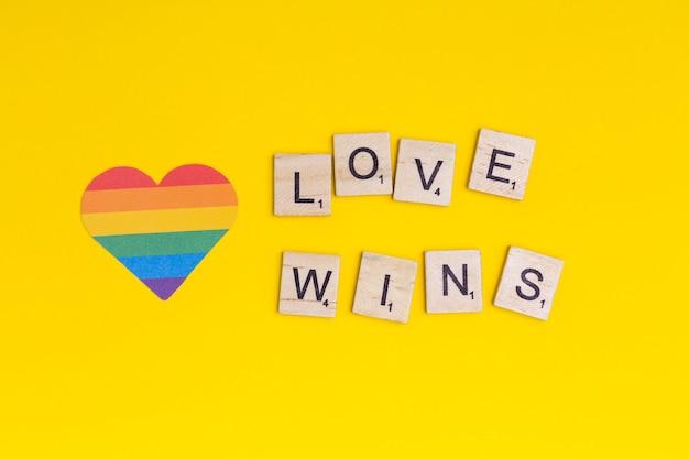 Lgbt hart pictogram en woord liefde wint op houten blokken Gratis Foto