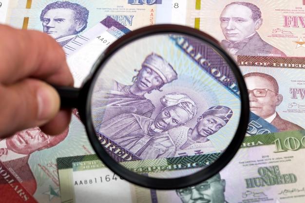Liberiaans geld in een vergrootglas een bedrijfsachtergrond Premium Foto