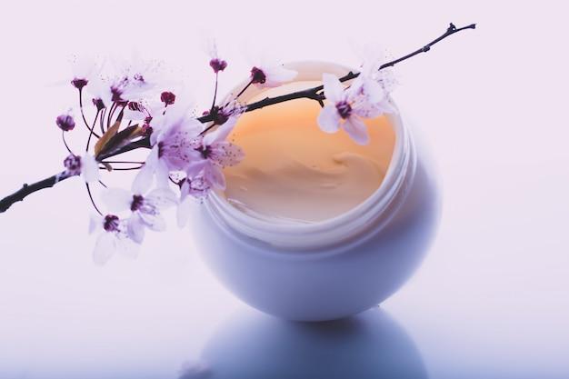 Lichaamscrème en bloemen op een lichte achtergrond Premium Foto