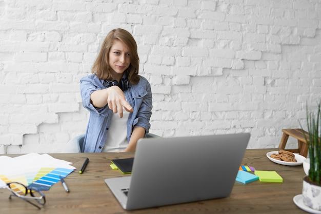 Lichaamstaal en modern technologieconcept. emotionele jonge vrouw met koptelefoon om haar nek, zit open laptop, glimlachend en wijsvinger wijzend op het scherm, iets grappigs zien Gratis Foto