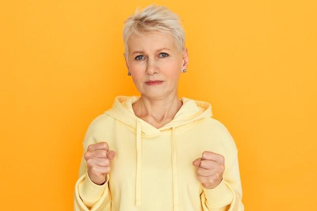 Lichaamstaal. geïsoleerd beeld van gefrustreerde, overstuur gepensioneerde vrouw met blond kort kapsel, gebalde vuisten, klaar om te vechten, haar kracht te tonen, poseren bij gele studiomuur met hoodie Gratis Foto