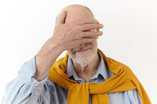 Lichaamstaal. geïsoleerde weergave van modieuze elegante senior zakenman met baard en kaal hoofd voor ogen met een handpalm tijdens het spelen met zijn kleinzoon. rijpe oude man schaamt zich Gratis Foto