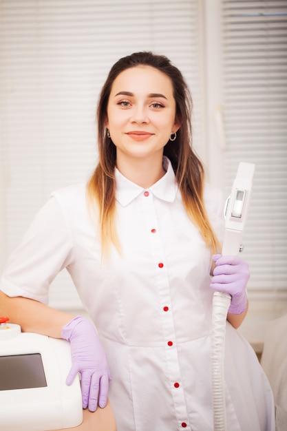 Lichaamsverzorging. vrouw arts die machine voor de verwijdering van het laserhaar toont Premium Foto
