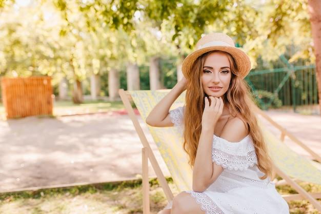 Licht gebruind meisje in vintage kanten jurk zittend in tuinstoel en poseren met interesse. knappe jonge vrouw in zomer strooien hoed ontspannen onder de blote hemel en zachtjes glimlachen. Gratis Foto