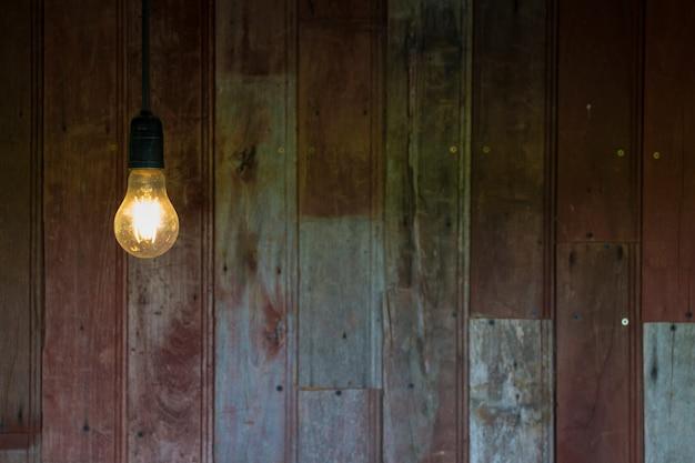 Licht van vintage gloeilamp met oude houten muur achtergrond, afbeelding met kopie ruimte. Premium Foto
