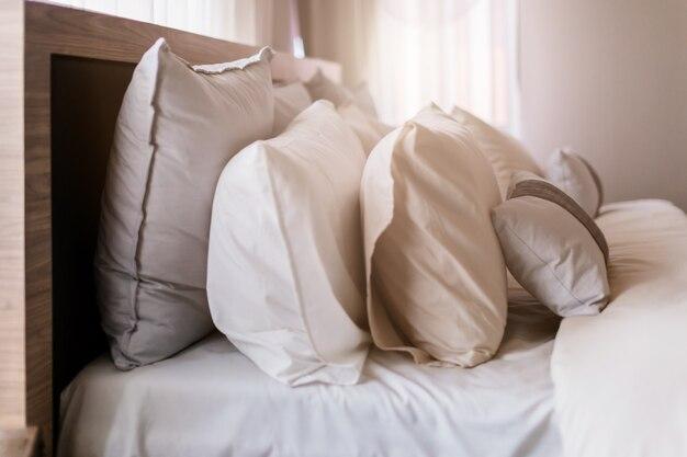 licht zacht kussen op mooi bed gezellige slaapkamer met zonlicht van raam interieur concep premium foto